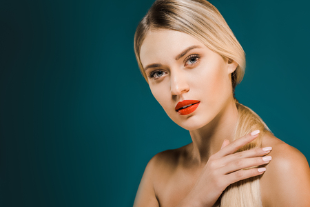 portrait of beautiful blond woman with red lips and shoulders on dark background