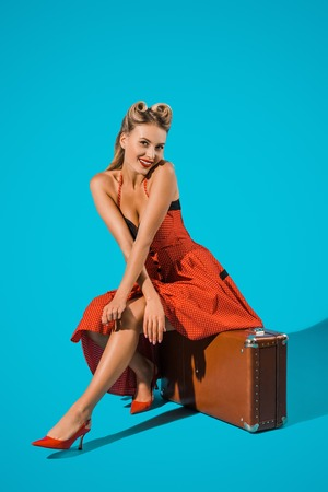 smiling pin up woman in retro dress sitting on suitcase on blue backdrop