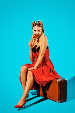 pretty pin up woman in retro style dress with lollipop sitting on suitcase on blue backdrop Banco de Imagens