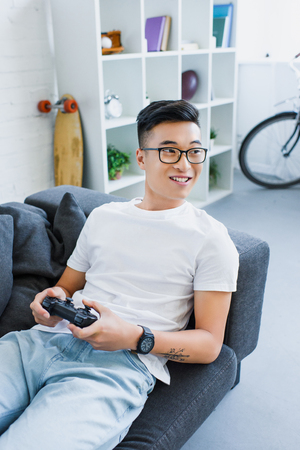 smiling handsome asian man playing video game and lying on sofa at home