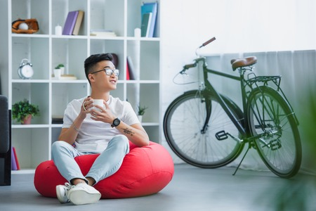 handsome asian man sitting on bean bag chair with cup of tea and looking away at home