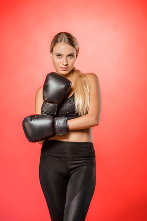 attractive sportswoman posing with boxing gloves isolated on red Archivio Fotografico