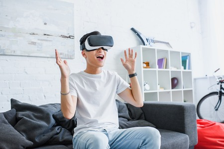 happy young asian man sitting on couch and using virtual reality headset at home 写真素材