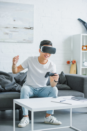 excited young man in virtual reality headset playing with joystick at home 写真素材