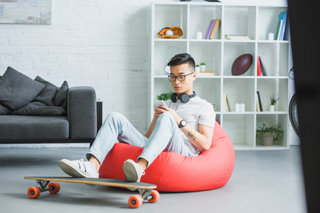handsome young asian man sitting in bean bag chair and using smartphone at home