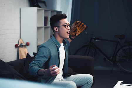 emotional young asian man with baseball glove and ball sitting on couch and watching sport match at home Imagens