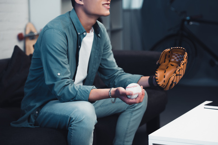 cropped shot of young man with baseball glove and ball sitting on couch and watching sport match at home