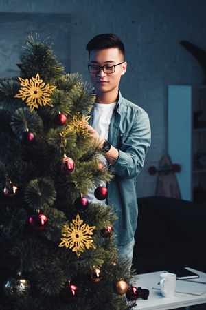 young asian man in eyeglasses decorating christmas tree at home