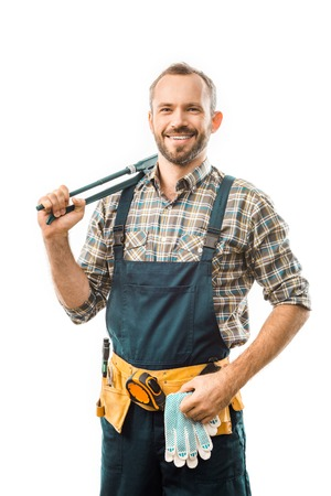 smiling plumber with tool belt holding monkey wrench and looking at camera isolated on white Stok Fotoğraf