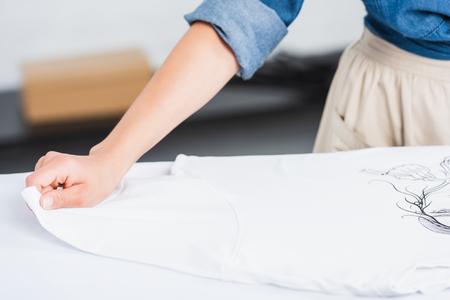 Zugeschnittenes Bild einer Designerin, die ein weißes T-Shirt mit Aufdruck auf das Bügelbrett legt putting