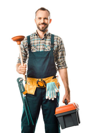 smiling handsome plumber holding plunger and toolbox isolated on white, looking at camera Stockfoto - 110524899
