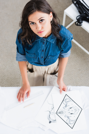 overhead view of female fashion designer looking at camera and measuring space for print on empty white t-shirt