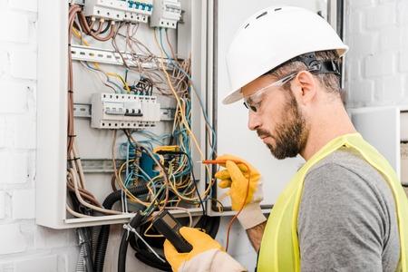 Gut aussehender Elektriker, der den Stromkasten mit Multimeter im Flur überprüft Standard-Bild