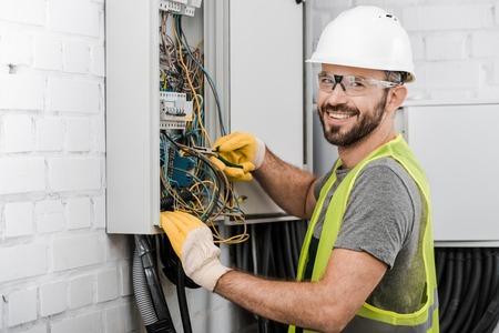 Lächelnder gutaussehender Elektriker, der einen Elektrokasten mit einer Zange im Korridor repariert und in die Kamera schaut Standard-Bild