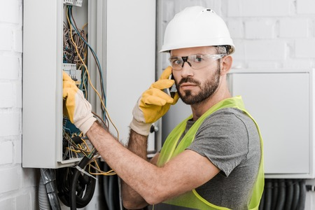surprised electrician checking electrical box and talking by smartphone in corridor