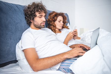 young couple using laptop and smartphone while lying in bed in bed
