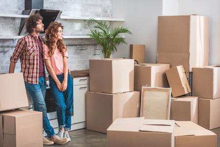 vriendin en vriend met krullend haar staan in de buurt van kartonnen dozen en kijken weg naar nieuwe keuken