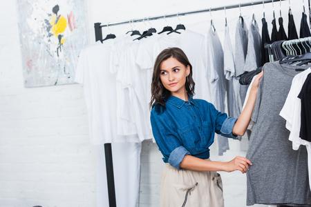 smiling female designer taking grey t-shirt from hanger in clothing design studio Stock fotó