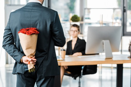 cropped image of businessman hiding bouquet of roses behind back to surprise businesswoman in office