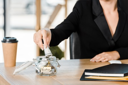 cropped image of businesswoman putting money in glass jar with note Vacation in office, travel concept