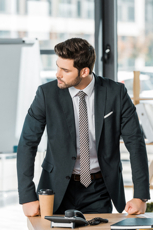 handsome businessman leaning on table in office and looking away