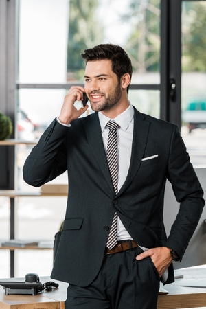 smiling handsome businessman leaning on table and talking by smartphone in office