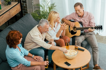 high angle view of happy old friends spending time with guitar and beer at home Banco de Imagens
