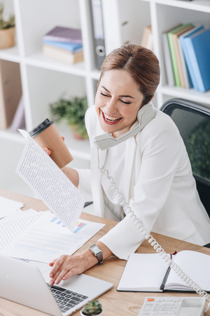 laughing businesswoman holding coffee to go while talking on phone and working with documents and laptop in office Stock Photo