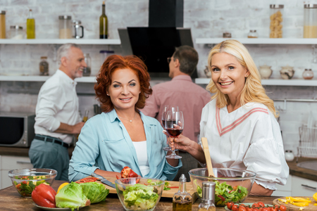 smiling beautiful women preparing salad for dinner, holding wineglasses and looking at camera at home