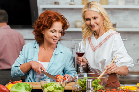 smiling attractive women preparing salad for dinner with wine at home