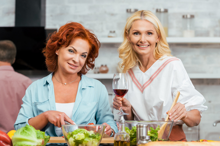 smiling attractive women preparing salad for dinner with wine and looking at camera at home