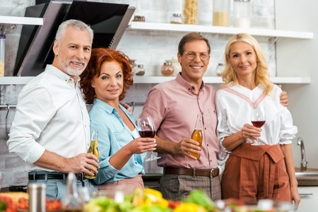happy mature friends holding glasses of wine and beer bottles, smiling at camera in kitchen Stok Fotoğraf