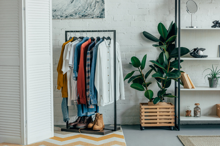 different shirts on hangers, shoes on shelf in living room 스톡 콘텐츠