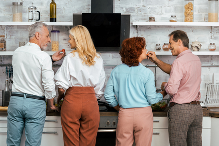 back view of men feeding mature women while standing together in kitchen Banque d'images - 110515083