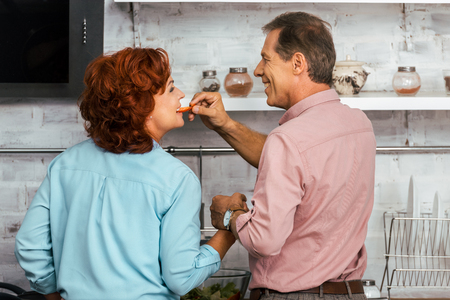 back view of smiling man feeding beautiful mature woman while standing together in kitchen