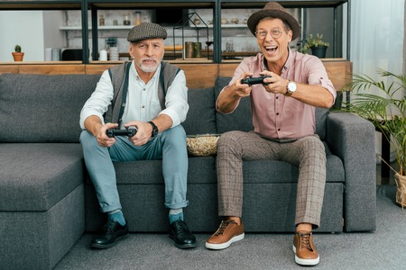 handsome mature men sitting on sofa and playing with joysticks Banco de Imagens