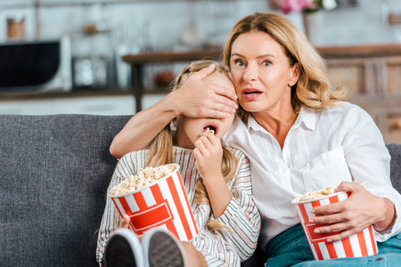 frightened mother and daughter with buckets of popcorn watching scary movie at home