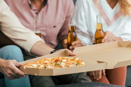 cropped shot of man holding pizza box and friends drinking beer behind