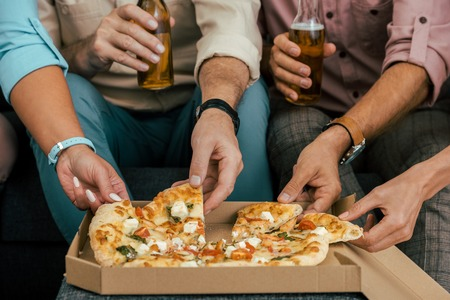 cropped shot of mature friends drinking beer and eating pizza together
