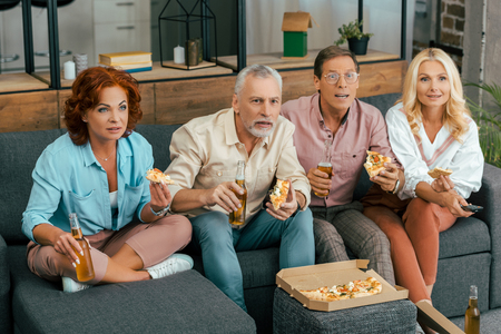 high angle view of mature friends sitting on sofa, drinking beer and eating pizza while watching tv at home