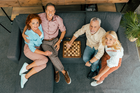 overhead view of mature friends playing chess and smiling at camera