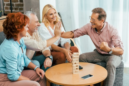 happy mature men giving high five while playing with wooden blocks at home