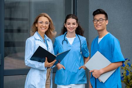 smiling teacher with two multicultural students looking at camera at medical university