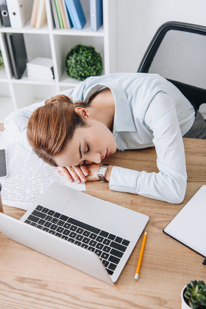 high angle view of adult businesswoman sleeping at workplace in modern office