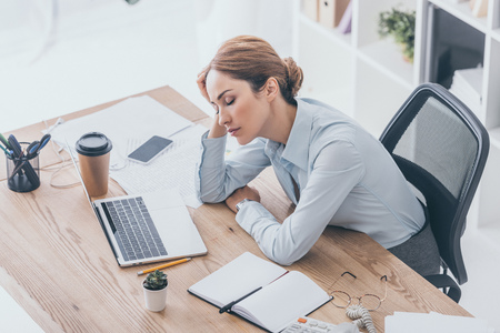 high angle view of exhausted adult businesswoman sleeping at workplace in modern office