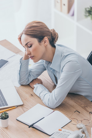 high angle view of overworked adult businesswoman sleeping at workplace in modern office Stock Photo