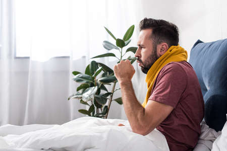 side view of sick young man having cough while sitting in bed