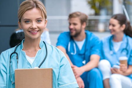 smiling medical student standing with notebook and looking at camera