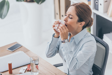 high angle view of diseased adult businesswoman sneezing at workplace Standard-Bild