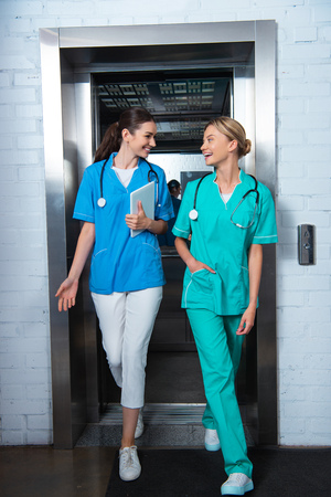 smiling medical students walking from elevator and looking at each other